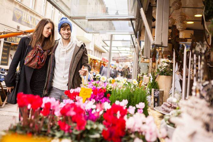 Ein junges Pärchen - Mann und Frau - schlendern über den Wiener Brunnenmarkt. Im Fordergrund ein Marktstand mit Tulpen. Foto von Stephan Doleschal.