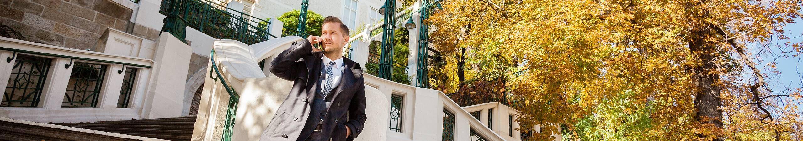 Mann, gekleidet in einen Anzug, steht am unteren Ende der Strudlhofstiege und telefoniert. Im Hintergrund leuchtet ein Laubbaum in herbstlichen Farben. Foto von Stephan Doleschal.