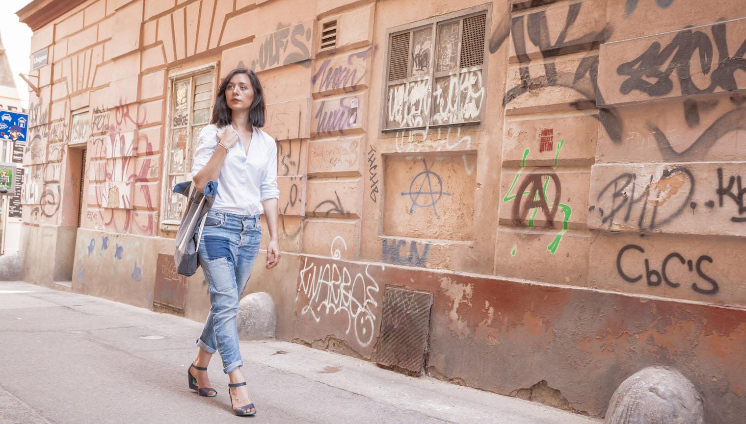 Eine junge Frau mit Jeans und weißer Bluse geht in Wien an einer besprayten Hausmauer vorbei.