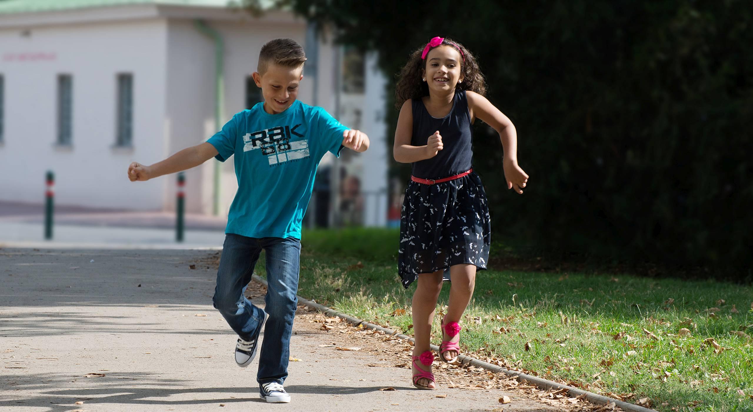 Ein Bub und ein Mädchen laufen fröhlich einen Weg entlang. Foto von Ernst Grünwald