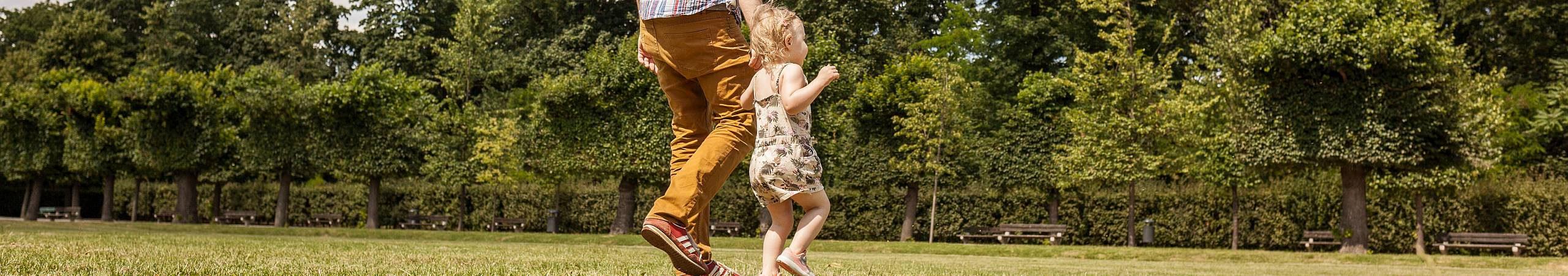 Ein Vater mit seiner 3 Jahre alten Tochter geht über eine grüne Wiese. Foto von Stephan Doleschal