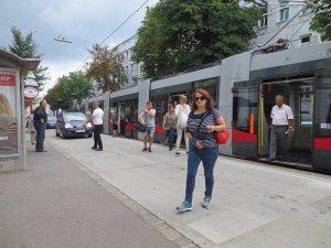 Menschen steigen aus der Straßenbahn aus. Sie betreten die Fahrbahn vor der Straßenbahn. Foto von Maria Grundner