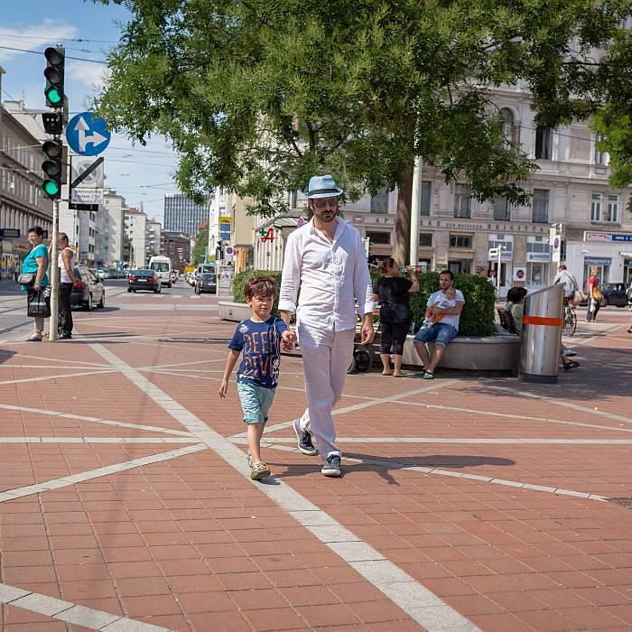 Ein Vater schlendert mit seinem Sohn an der Hand über den Wallensteinplatz.