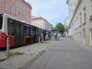 Eine Bushaltestelle in der gerade ein Bus steht. Ein Mann steigt ein. Foto von Maria Grundner