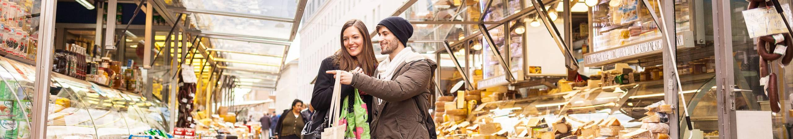 Ein junges Paar geht am Markt spazieren und erfreut sich an den frischen Produkten. Foto von Stephan Doleschal.