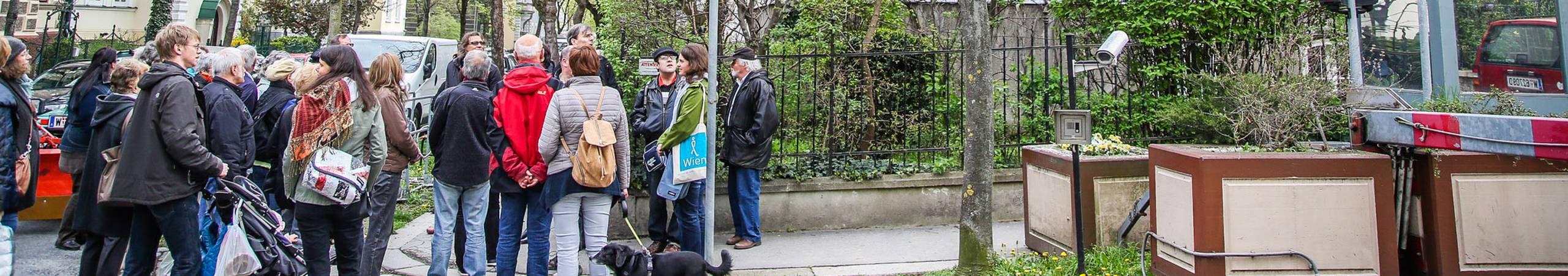 Petra Jens und Teilnehmer des Geh Cafes Währing stehen an einer Straßenecke und unterhalten sich über angrenzende Urban Gardening Beete. Foto von Christian Fuerthner