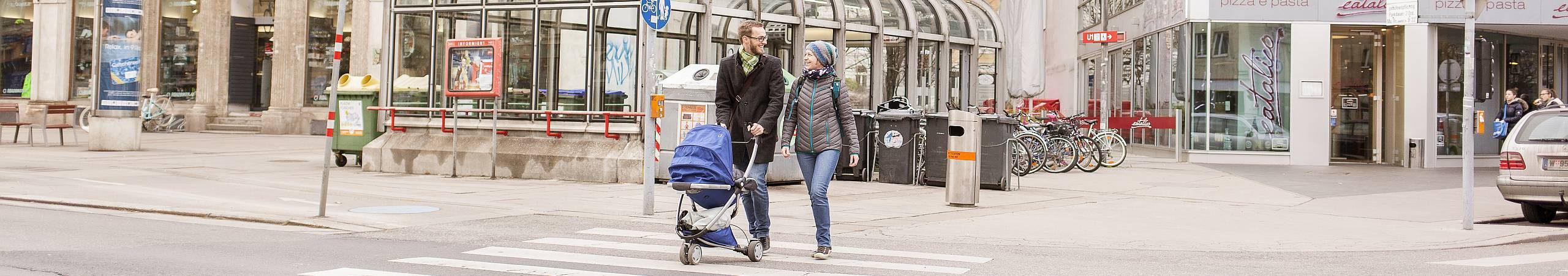 Ein lachendes Paar überquert mit Kinderwagen eine Kreuzung. Foto von Stephan Doleschal