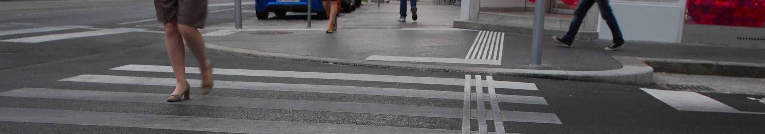 Eine Frau mit High Heels überquert an einem grauen Regentag die Straße. Foto von Gerd Götzenbrucker