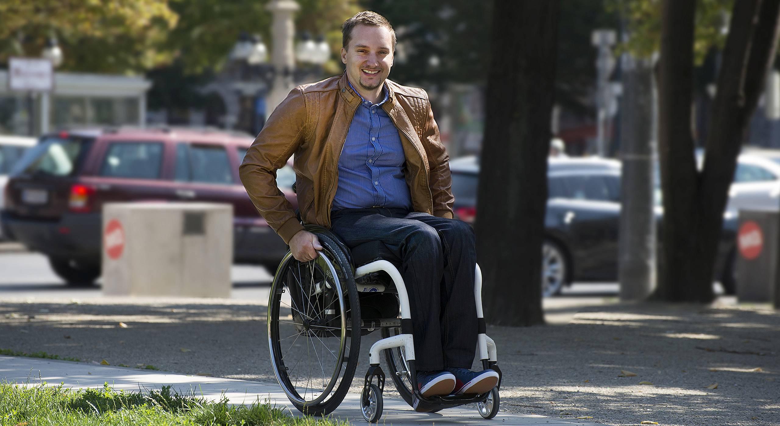 Ein Rollstuhlnutzer fährt durch einen Park in Wien. Foto von Ernst Grünwald