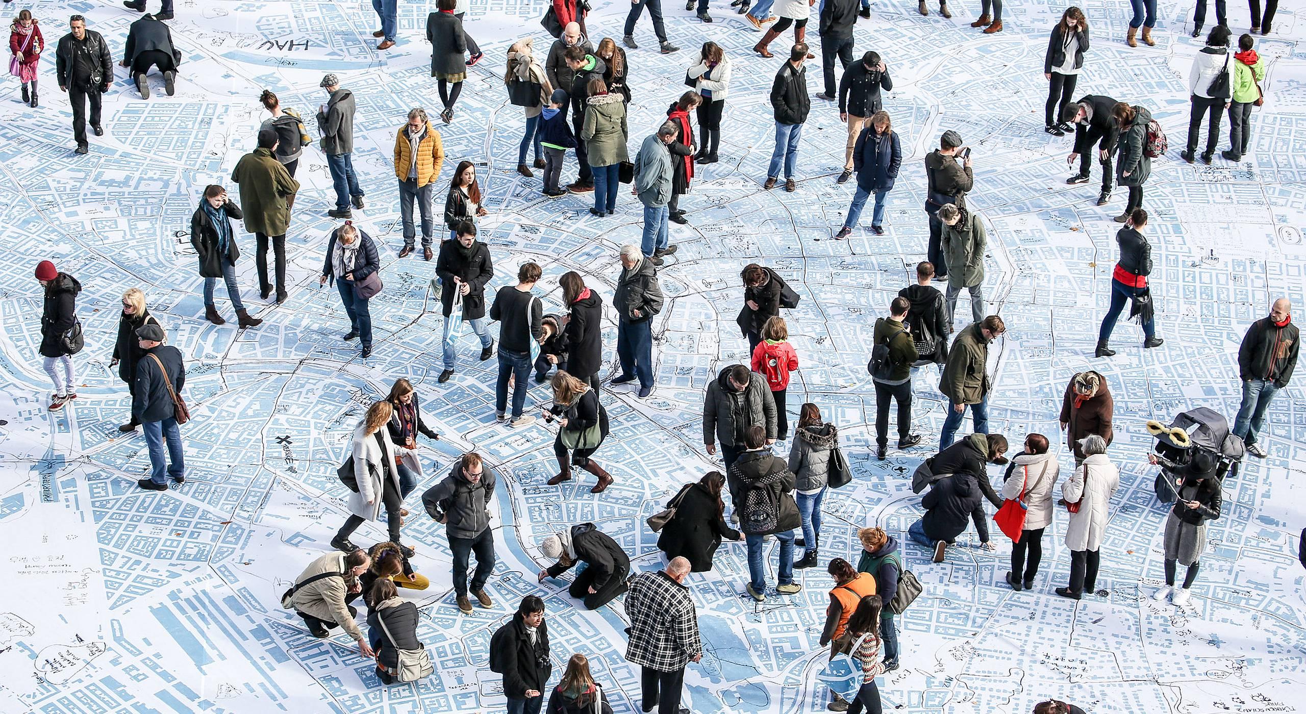 Etwa 50 Personen gehen, stehen und staunen über die größte Wienkarte aller Zeiten am Wiener Rathausplatz.