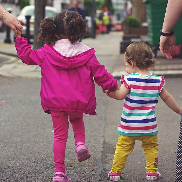 Zwei bunt angezogene Kinder gehen an der Hand ihrer Eltenrn über die Straße.