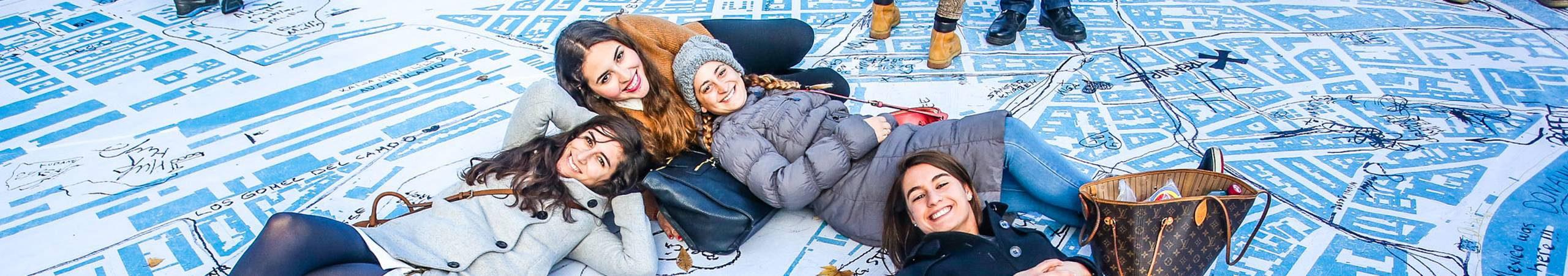 Vier junge Freundinnen posieren lachend vor der größten Wienkarte aller Zeiten am Rathausplatz. Foto von Christian Fuerthner