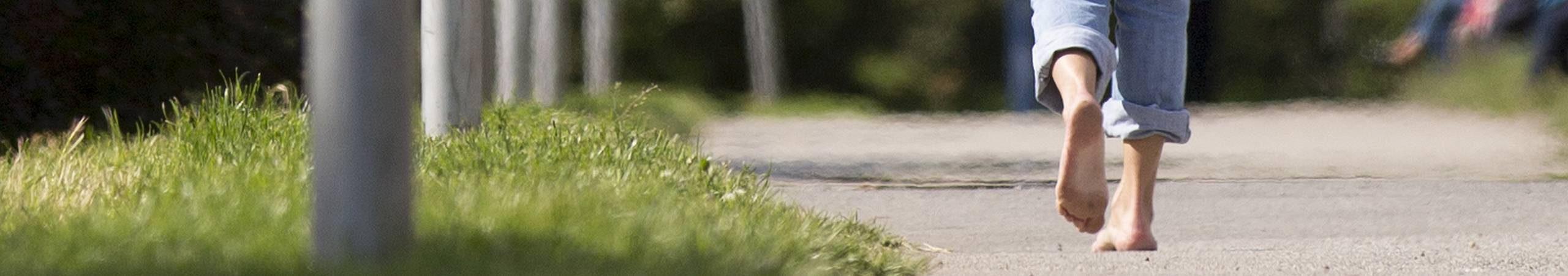 Eine Frau geht barfuß durch einen Wiener Park. Foto von Sebastian Philipp