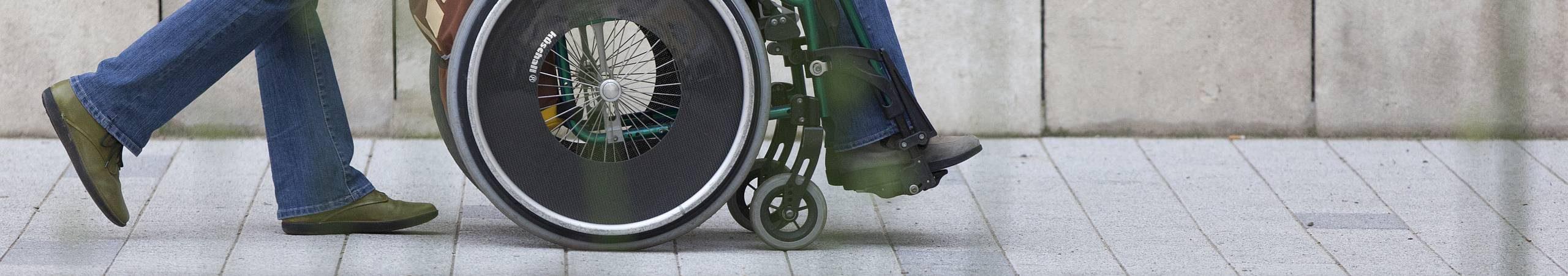 Ein Fußgänger fährt mit einem Rollstuhlnutzer durch die Stadt. Foto von Sebastian Philipp