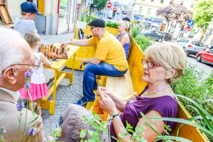 Eine Grätzloase im 7. Bezirk. Im gelben Garten, einem Parklet (Kleiner Park in der Parkspur), sitzen Leute aus der Nachbarschaft spielen, plaudern und stricken.