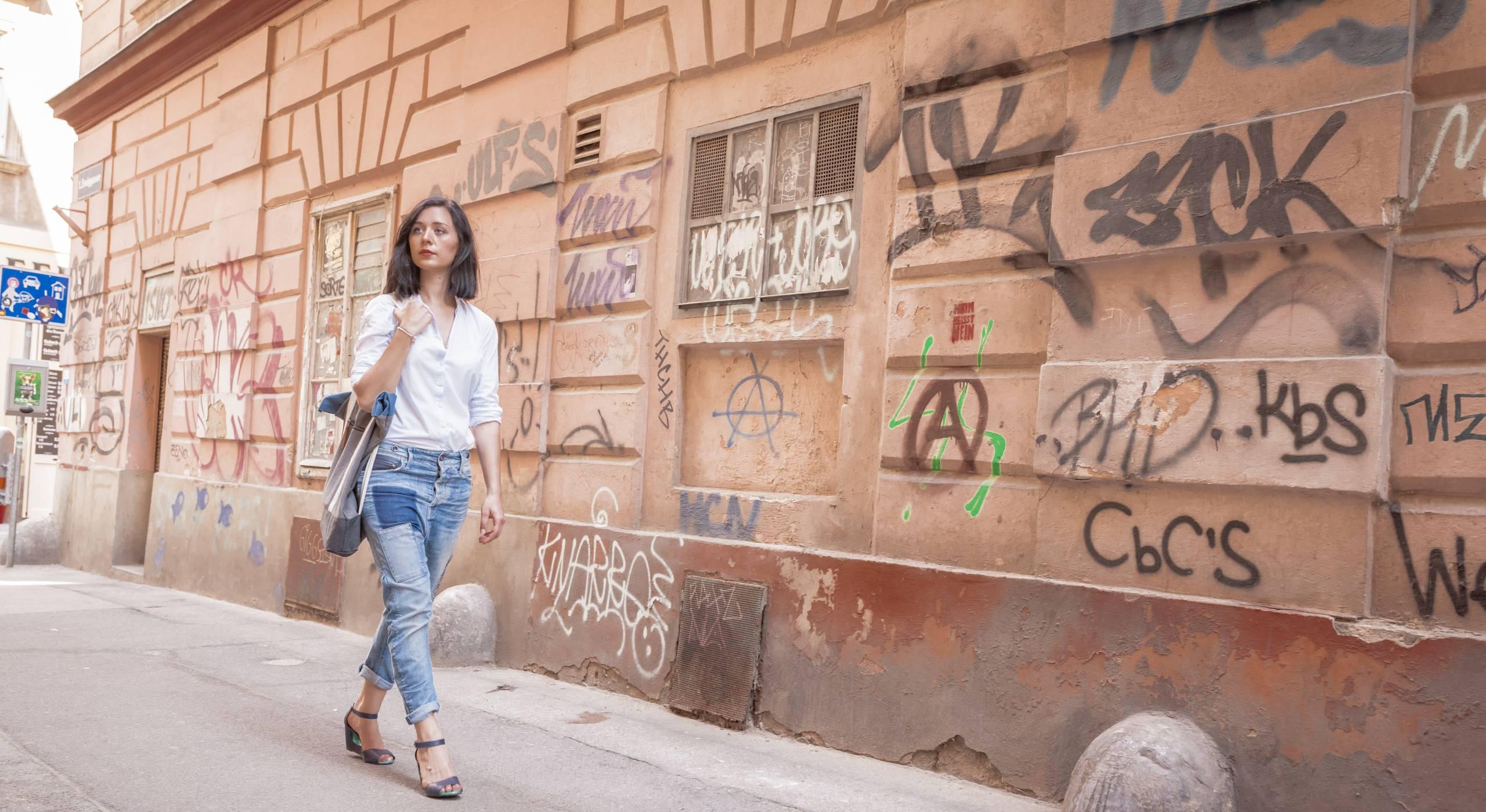 Eine junge Frau geht an einer braunen, mit GrEine junge Frau geht an einer mit Graffiti besprühten Wand vorbei. Foto von Stephan Doleschal