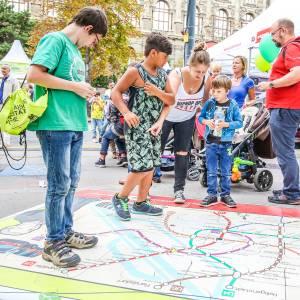 Menschen gehen zu Fuß über einen überdiemensionalen U-Bahnplan der Wiener Linien, der auf der Straße liegt. Foto Christian Fürthner