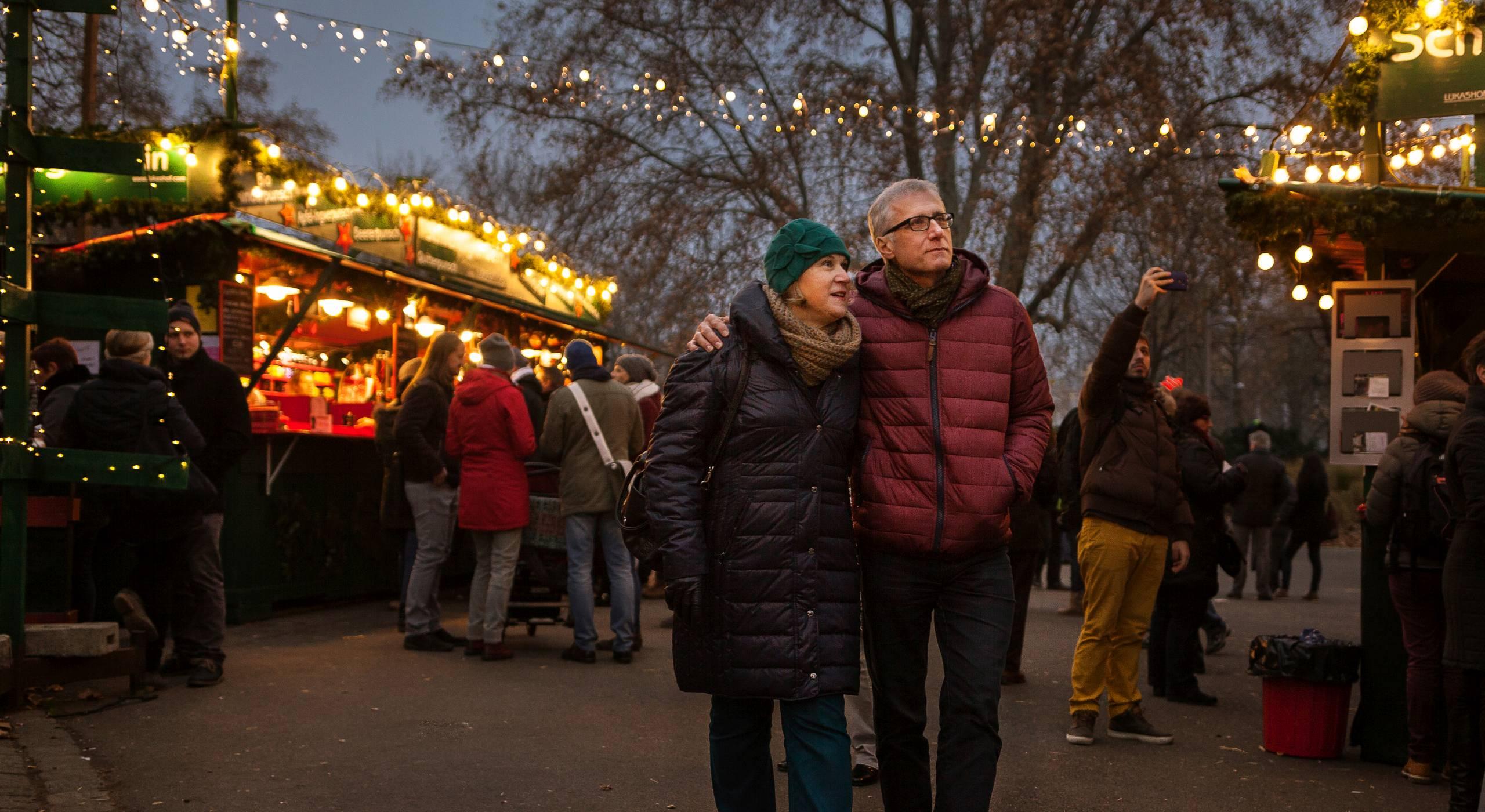 Ein Pärchen mittleren Alters in Winterkleidung flaniert Arm in Arm über einen Weihnachtsmarkt. Im Hintergrund sieht man bunt beleuchtete Marktstände. Foto: Stephan Doleschal