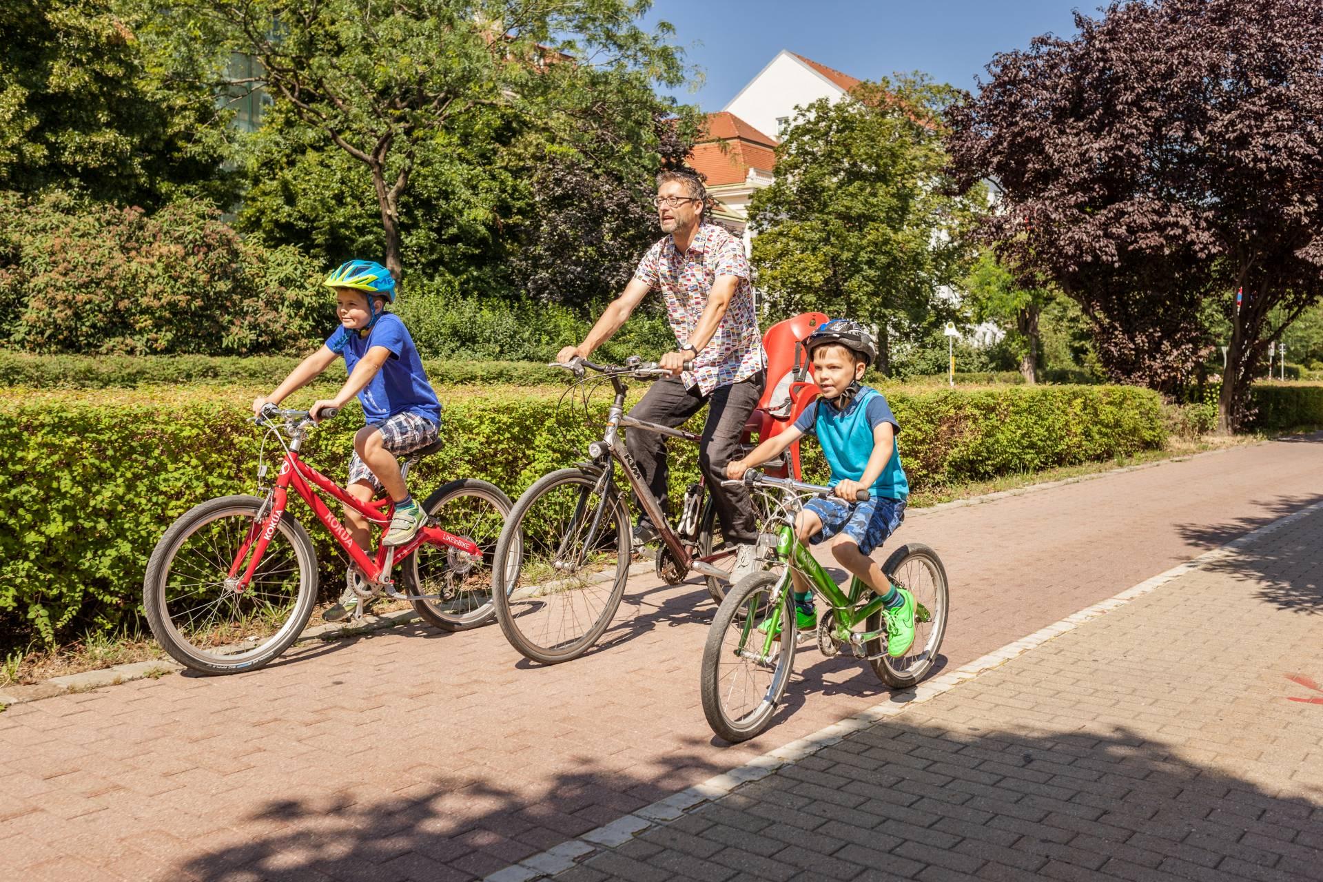 Ein Vater und seine beiden Söhne fahren gemeinsam Fahrrad. Foto: Stephan Doleschal