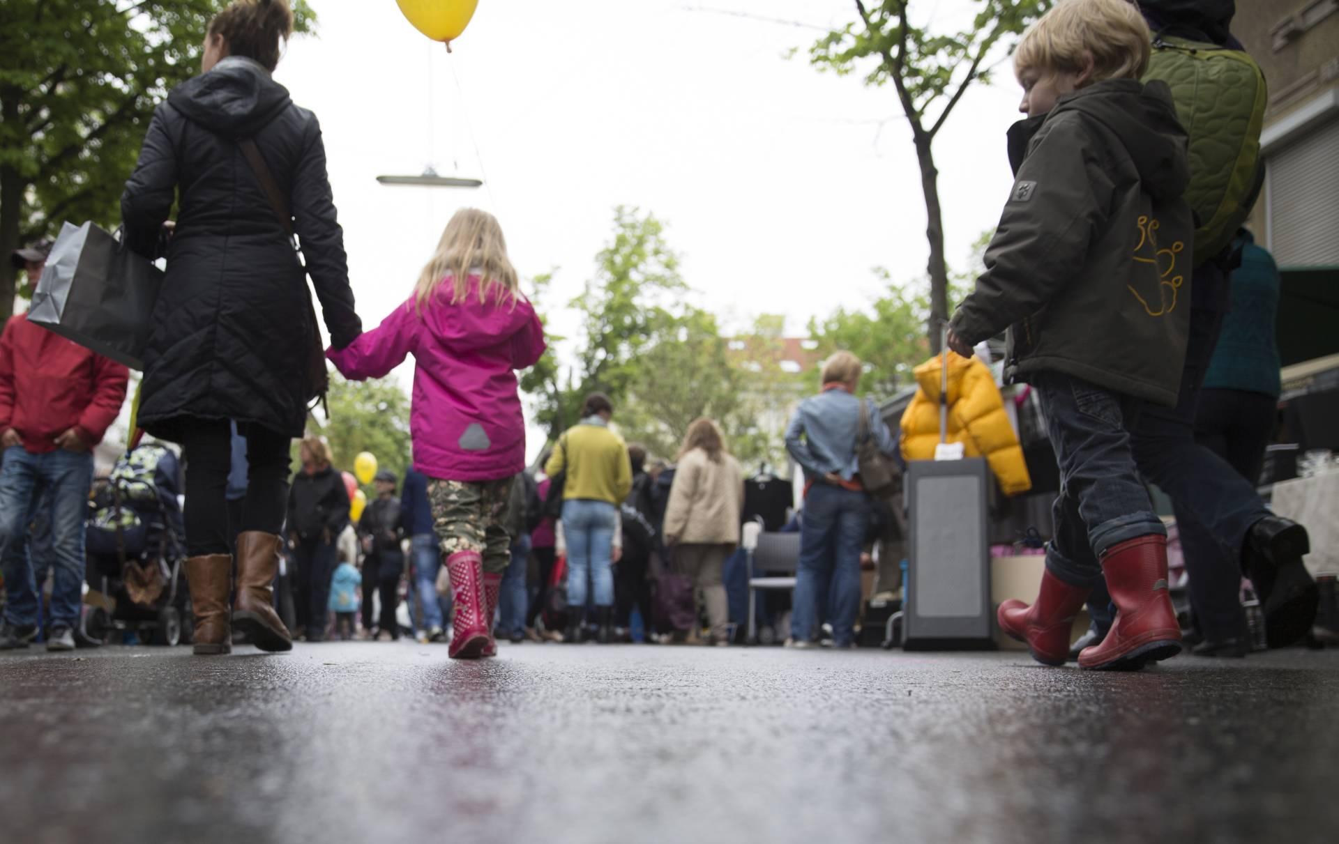 Mutter und Kind gehen Hand in Hand durch den Regen. Kind trägt Gummistiefel und rosa Regenjacke. Foto: Sebastian Philipp