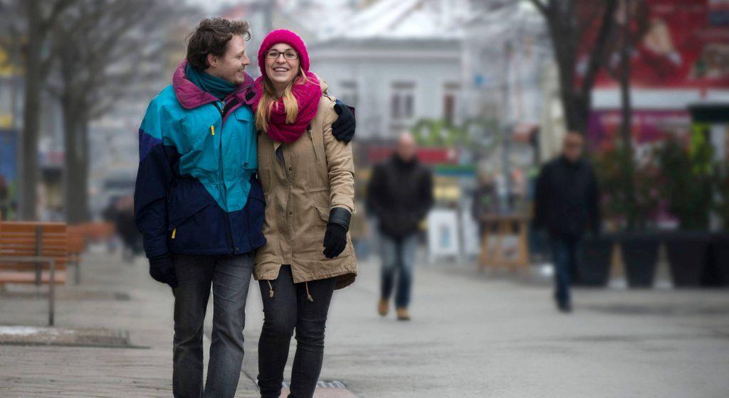 Ein junges Pärchen - Mann und Frau - geht in der winterlichen Meidlinger Hauptstraße spazieren. Er hat seinen Arm um ihre Schulter gelegt und lächelt sie verliebt an. Foto: Ernst Grünwald