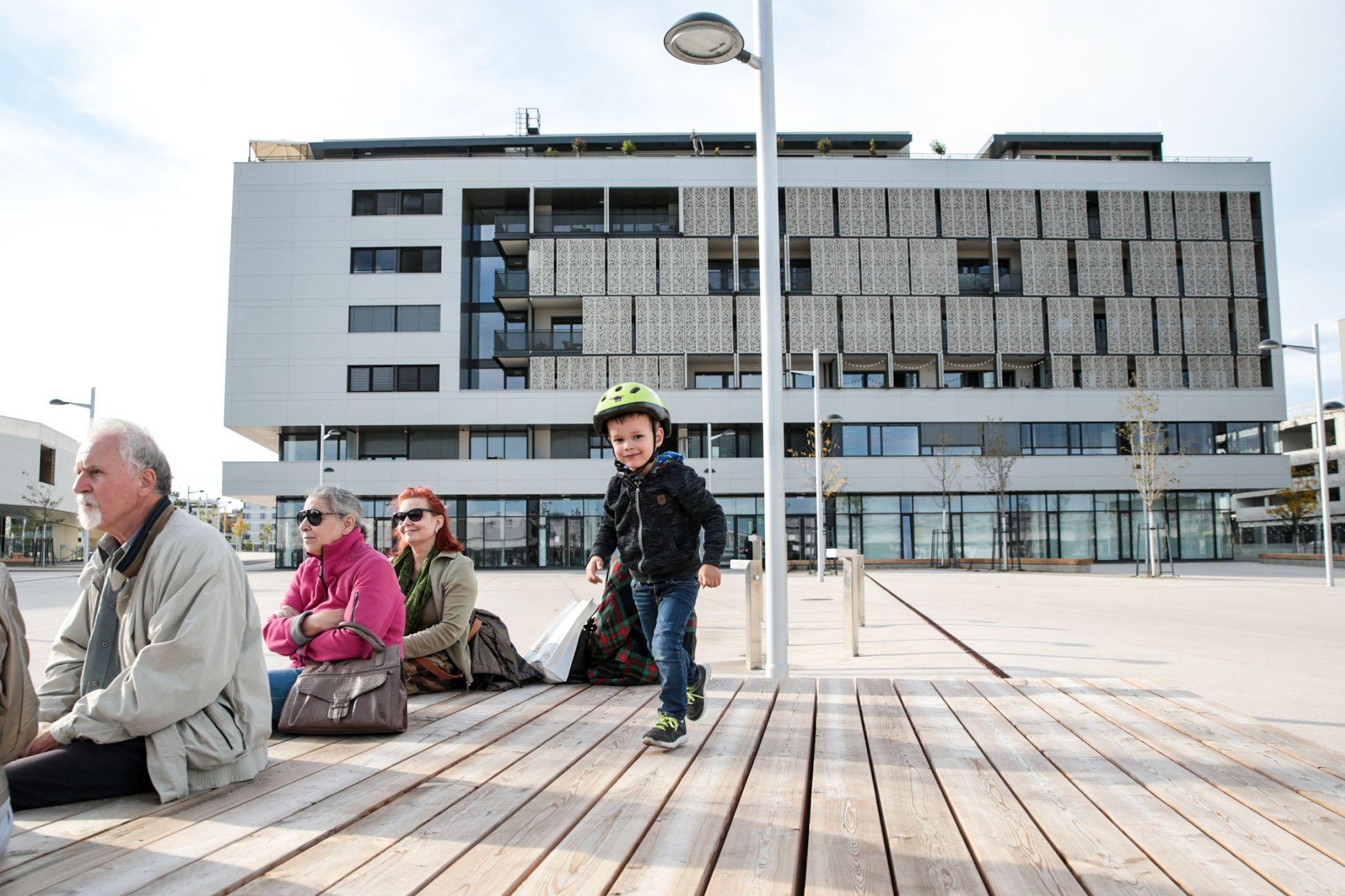 Sitzmöbel in der Seestadt Aspern. Ein kleiner Bub, zwei Frauen und ein Mann sitzen darauf. Foto: Mobilitätsagentur Wien/Christian Fürthner