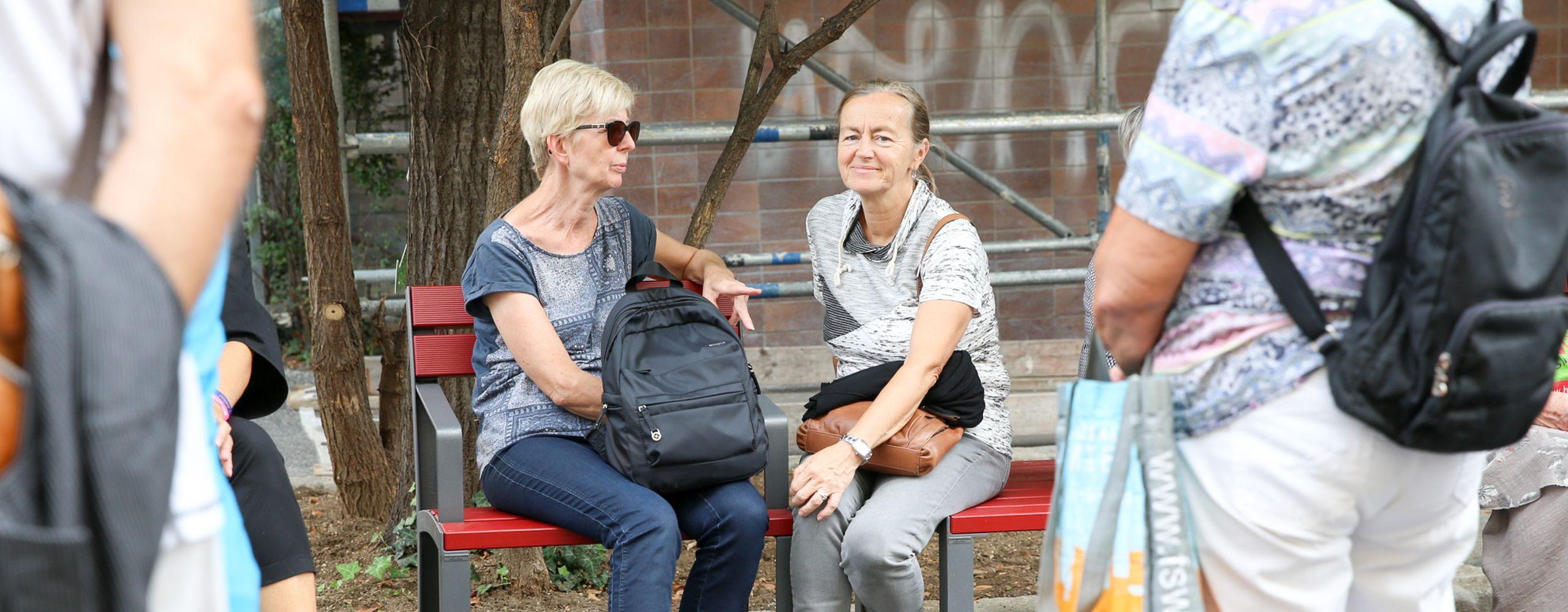 zwei Frauen sitzen auf einer roten Sitzbank. Foto: Mobilitätsagentur Wien/Christian Fürthner