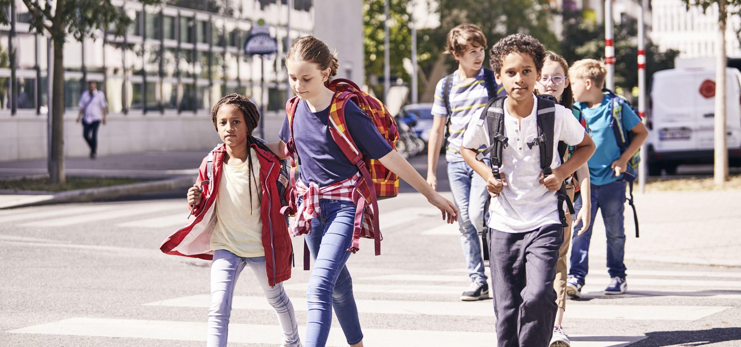 Fünf Kinder mit Rucksäcken auf dem Weg zur Schule