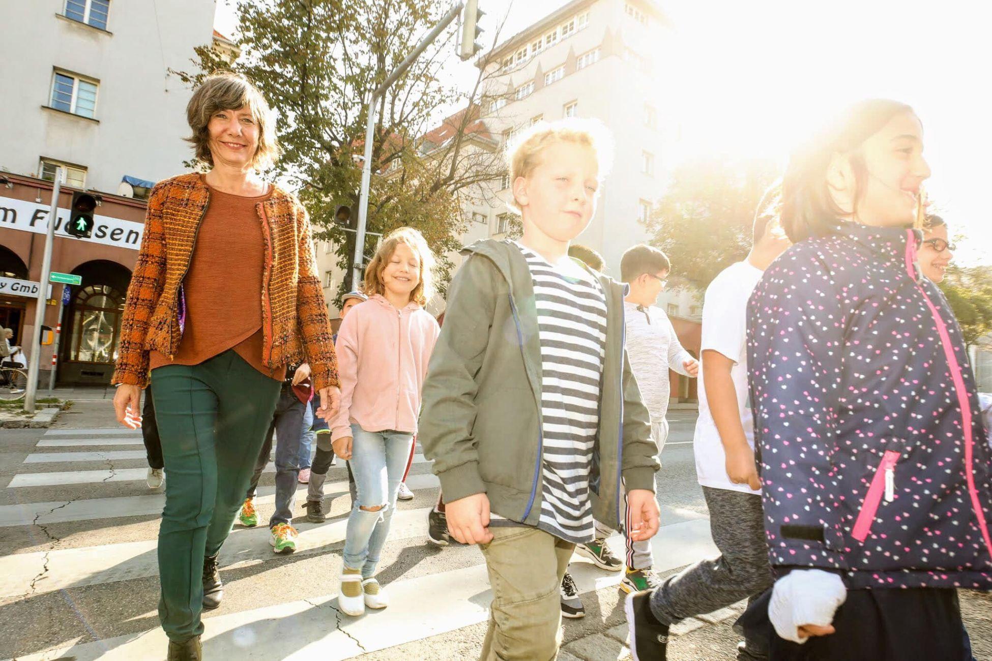 """Wiens 1. """"intelligente"""" Ampel ist im 12. Bezirk in Betrieb. Vizebürgermeisterin Birgit Hebein testet die Ampel gemeinsam mit Kindern der angrenzenden Volksschule."""