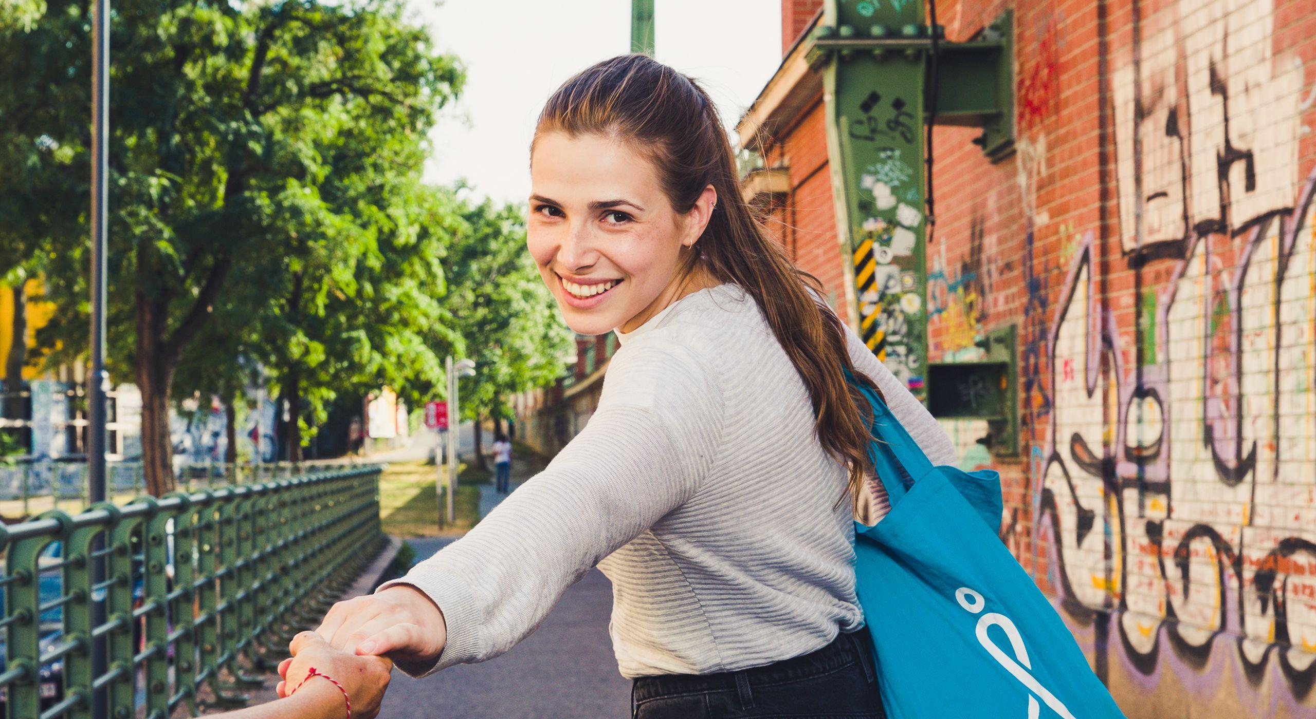 Junge Frau am Donaukanal. Sie lächelt in die Kamera und lädt zum Spazierengehen ein.
