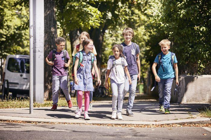 Kinder auf dem Schulweg zu Fuß.