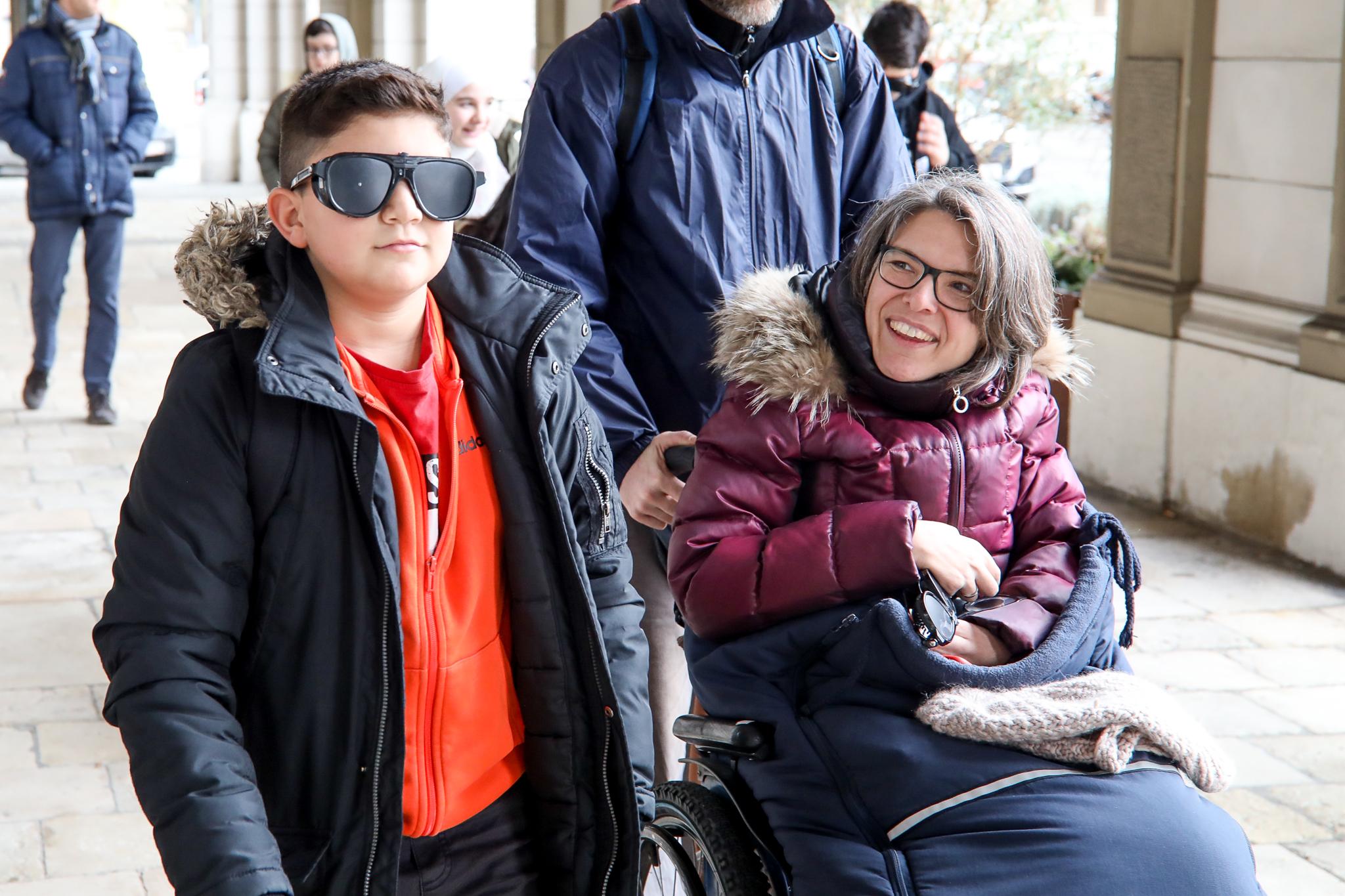 Ein Schüler geht mit einer Schlechtsehbrille. Maria Grundner, Expertin für Barrierefreiheit, fährt daneben mit dem Rollstuhl.