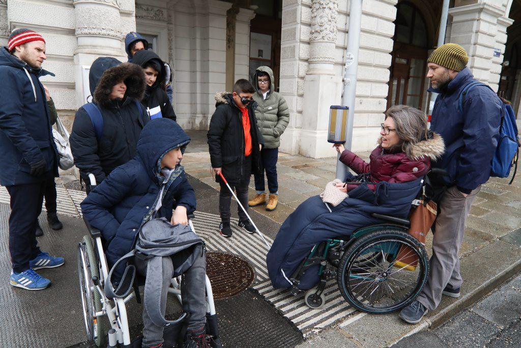 Maria Grundner erklärt an einer Ampel die Funktionweise einer akustischen Ampelanlage. Mehrere Schüler, darunter auch ein Junge, der einen Rollstuhl testet, hören ihr zu.