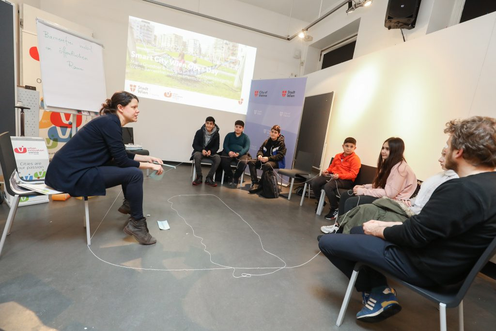 Veronika Gradnitzer sitzt mit mehreren Schülerinnen und Schülern in einem Raum. Eine Schnur ist teilweise am Boden ausgebreitet und wird von den Kindern gerhalten.