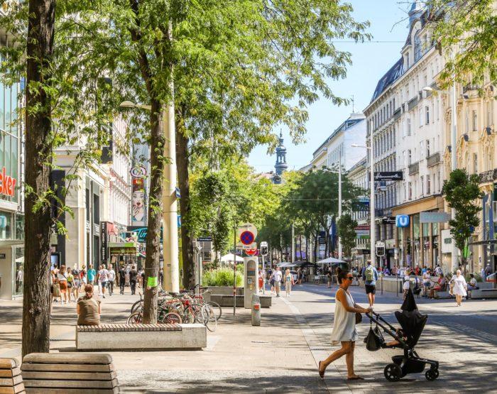 Frau schiebt Kinderwagen über die Fußgängerzone Mariahilfer Straße