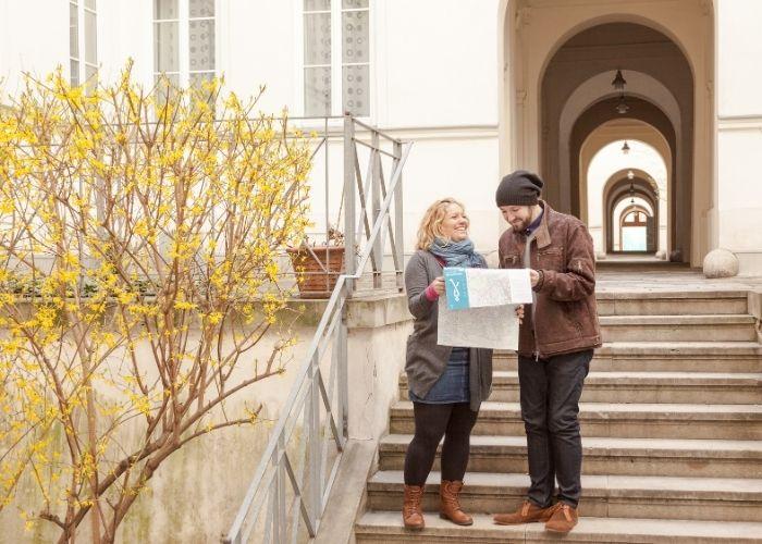 Eine Frau und ein Mann gehen in Wien spazieren und schauen auf der Fußwegekarte nach, wo sie sich gerade befinden.