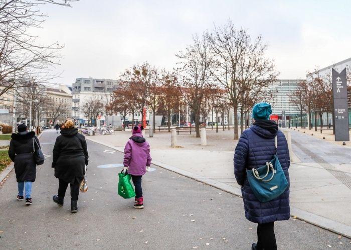 Fußgängerinnen und Fußgänger auf dem Gehweg vom Prater zu Messe Wien.