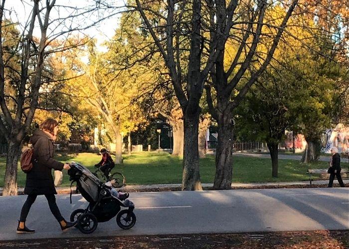 Frau schiebt einen Kinderwagen in der Parter Hauptallee
