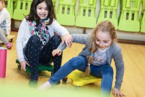 Kinder fahren in einem Parcours mit Rollbrettern