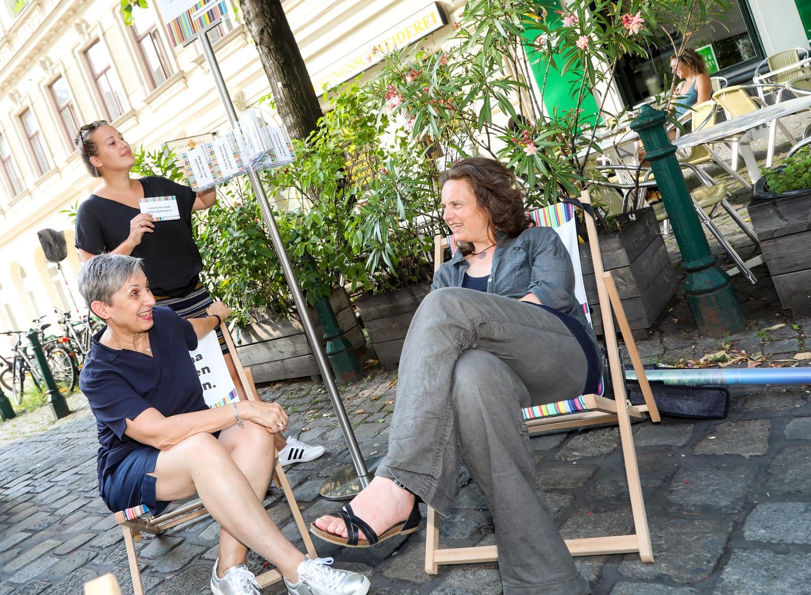 Drei Frauen sitzen auf Liegestühlen draußen, im Hintergrund ist es grün